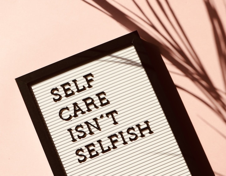 Self care isn't selfish sign on pink background