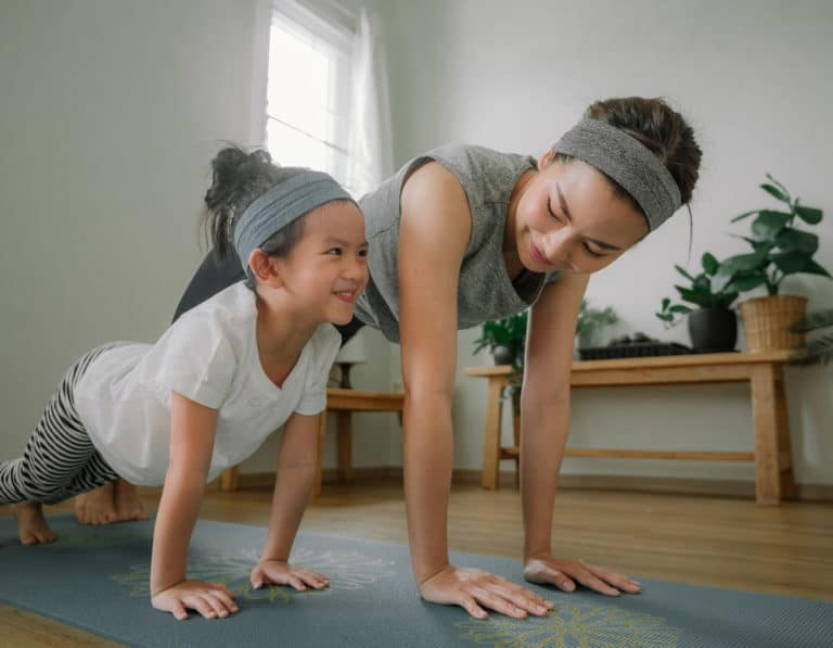 Mama and daughter working out with home fitness equipment