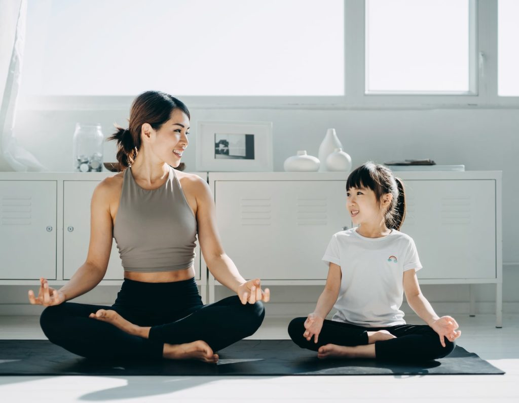 Family wellness goals for 2021, mama and children meditate on the sofa