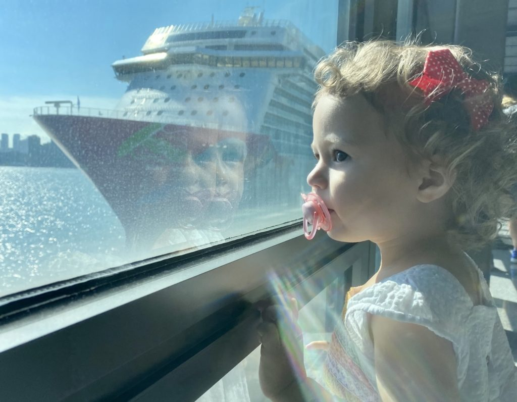 Cruise in Hong Kong, toddler looks out at the Genting Dream by Dream Cruises